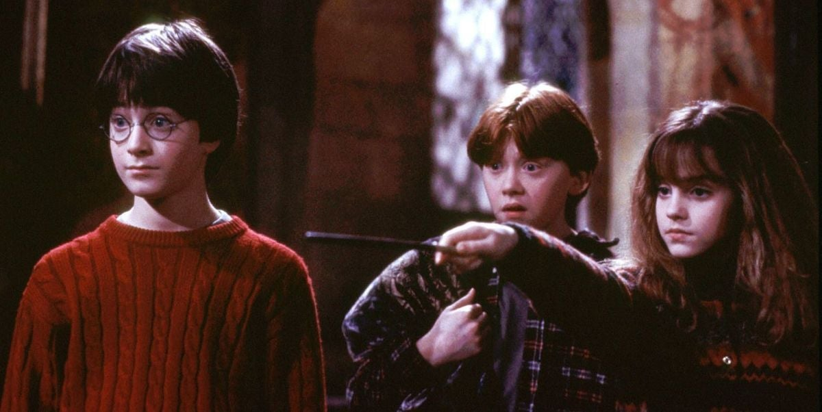 Three young adults have their eyes wide open while one holds a wand