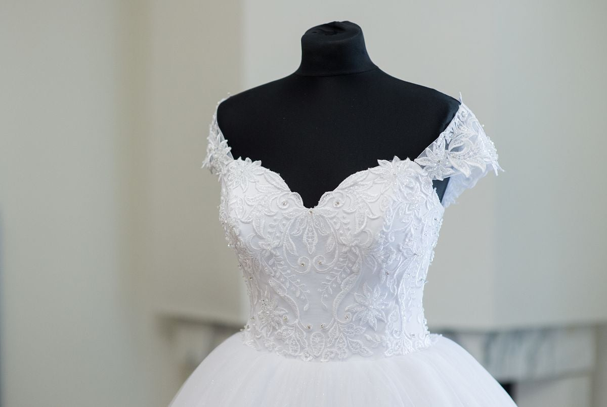An off-the-shoulder wedding dress with a lacy top and a big poufy skirt