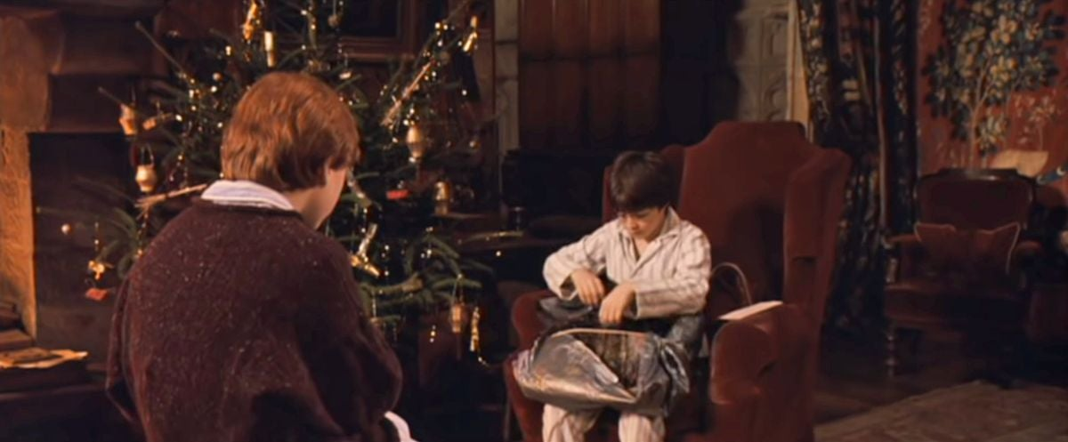 Harry opening a present near the Christmas tree as Ron looks on