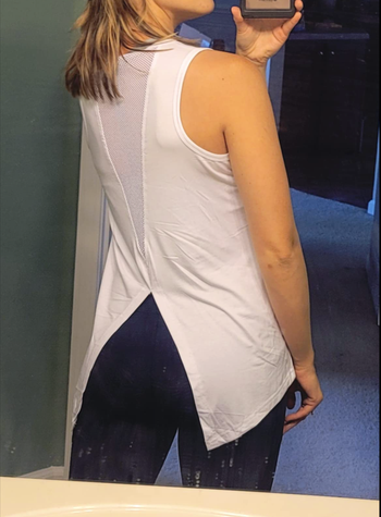 Reviewer showing the back of a white tank with a V-shaped mesh cut out and side flaps of fabric over the hips