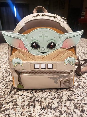 A mini back pack with baby yoda on the back and his ears sticking out