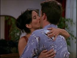 Monica and Chandler kiss in a living room