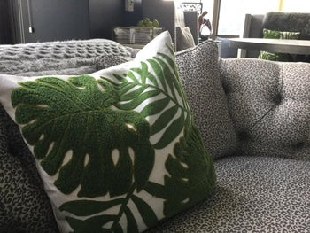 pillow with green and white leaf design cover on reviewer's couch