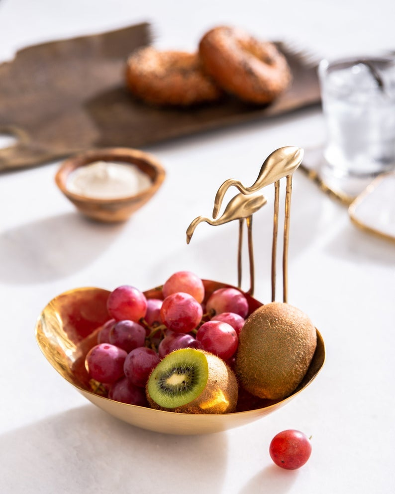 small bowl with flamingo sculptures on side holding grapes and kiwis