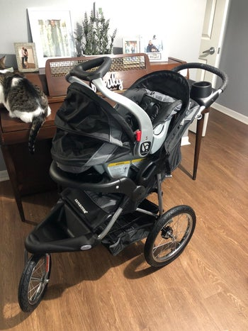a reviewer photo of the carseat on top of the jogging stroller in the color black