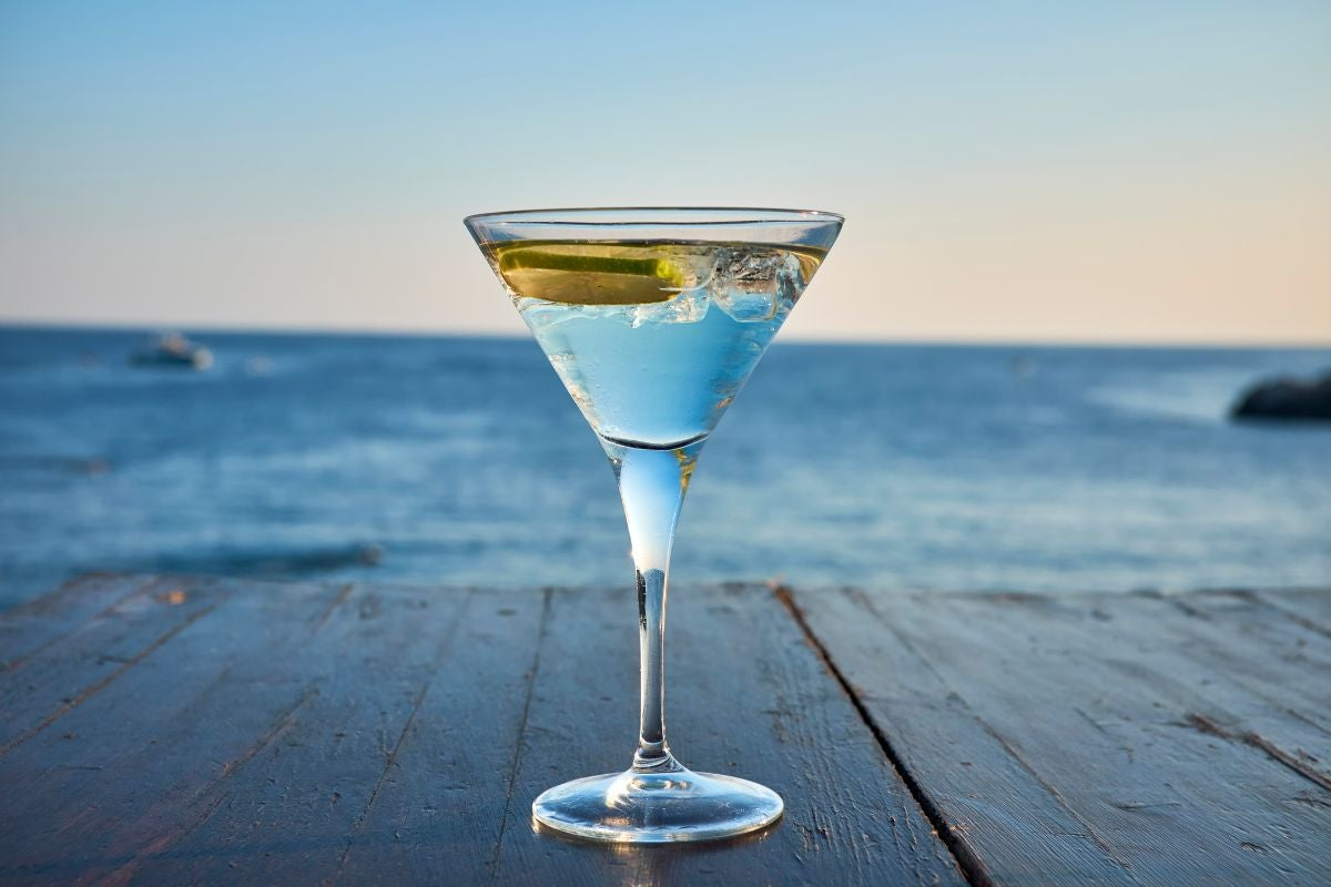 A clear and full martini glass in front of a seaside view