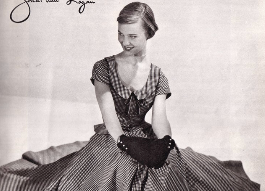 A woman sits and is sort of smiling. She has very short hair, above her ears. She wears a short-sleeved dress and is sitting on the ground.