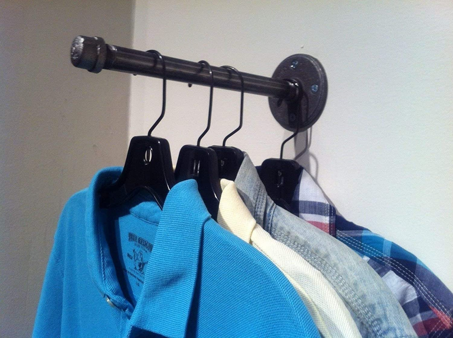 wall mounted rod with several shirts on a hanger on it