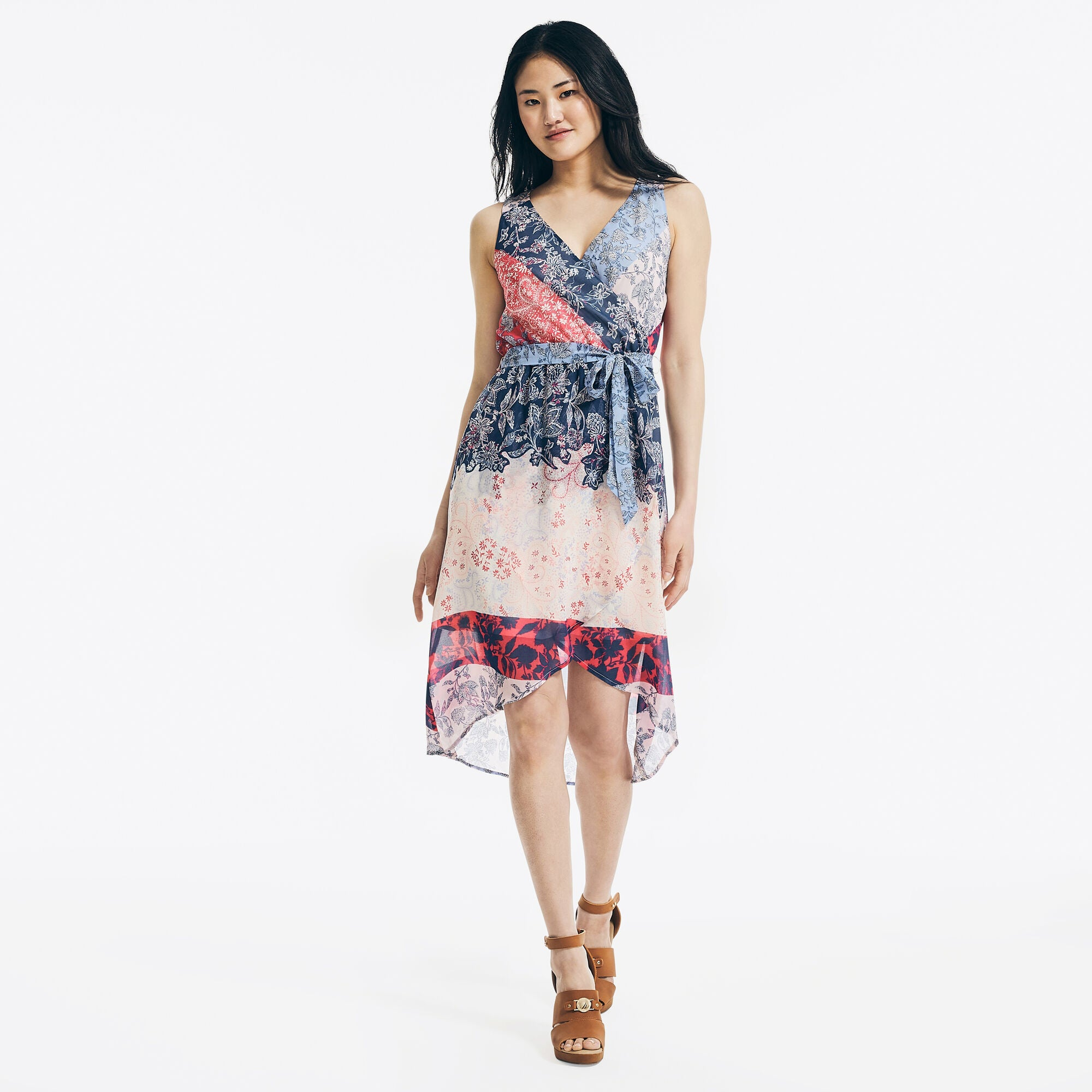 model in sleeveless wrap dress with sheer high-low hem that hits around the knees and has blue, red, and cream patterns