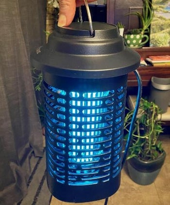 reviewer holding the bug zapper from its handle
