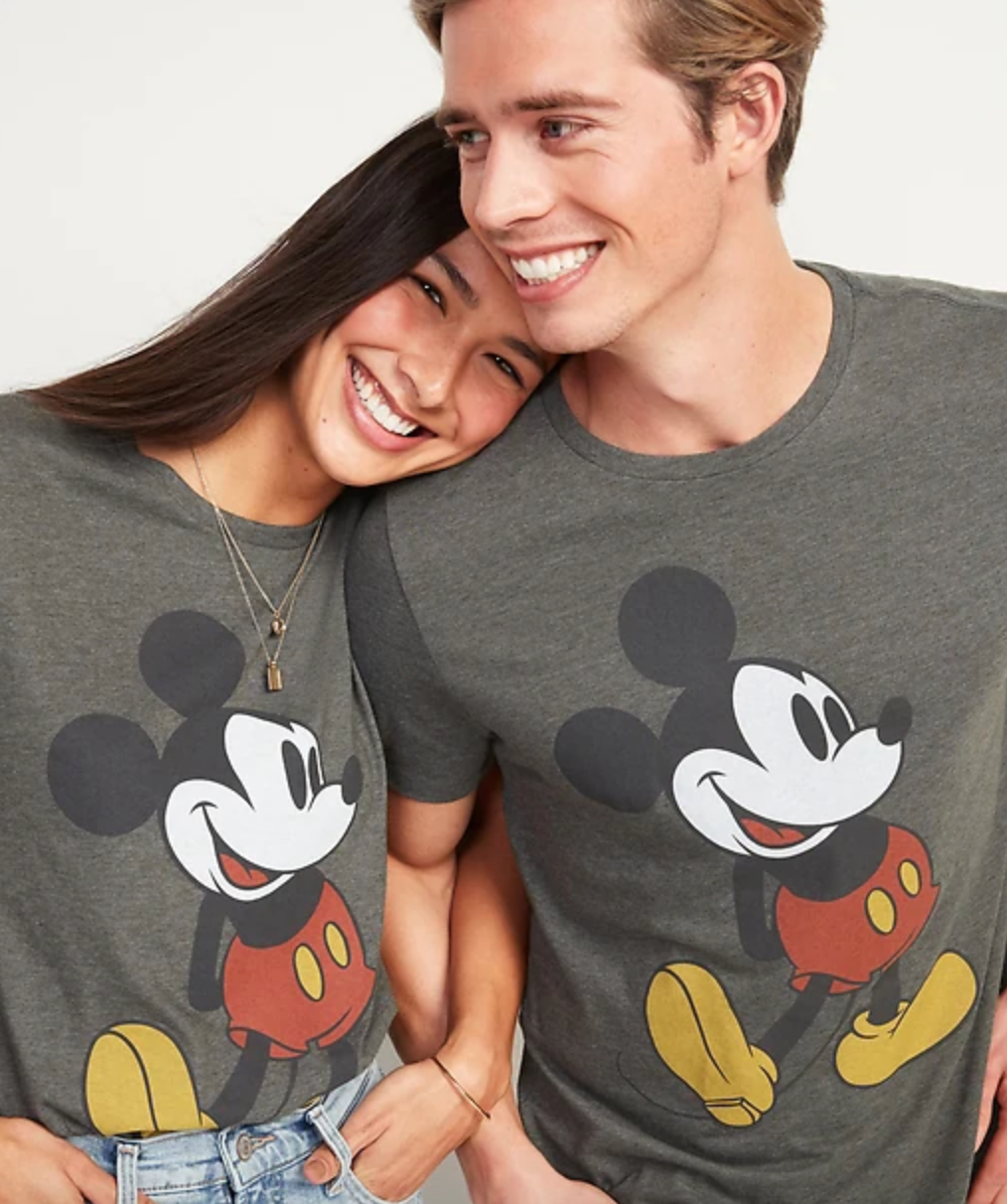 a man and a woman in gray t-shirts with mickey on them