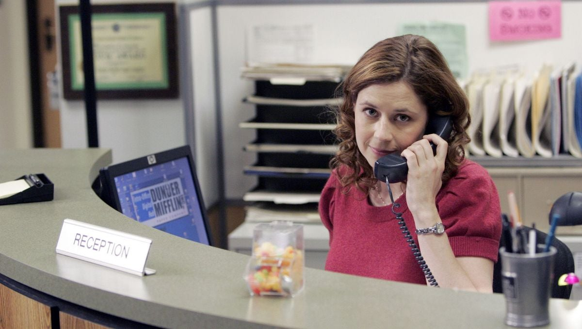 Pam Beesly is sitting at a desk, on the phone