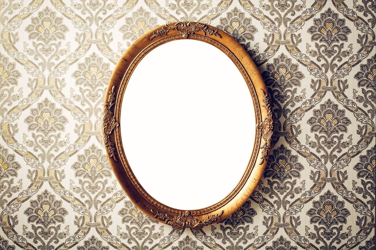 A round mirror with an intricate detailed frame