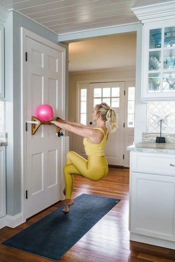 person using barre attached to the door to do exercises
