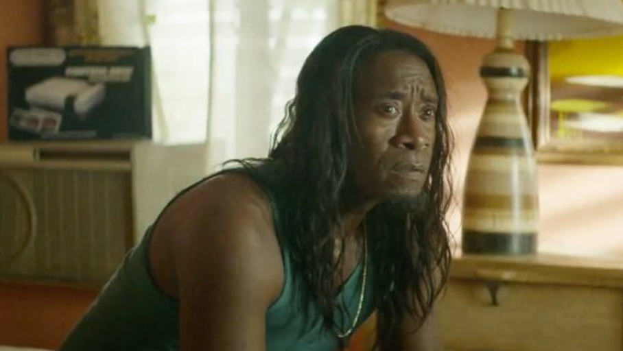 A man with a long wig is wearing a tank top and silver chain. He sits on a bed and his eyebrows are furrowed and raised