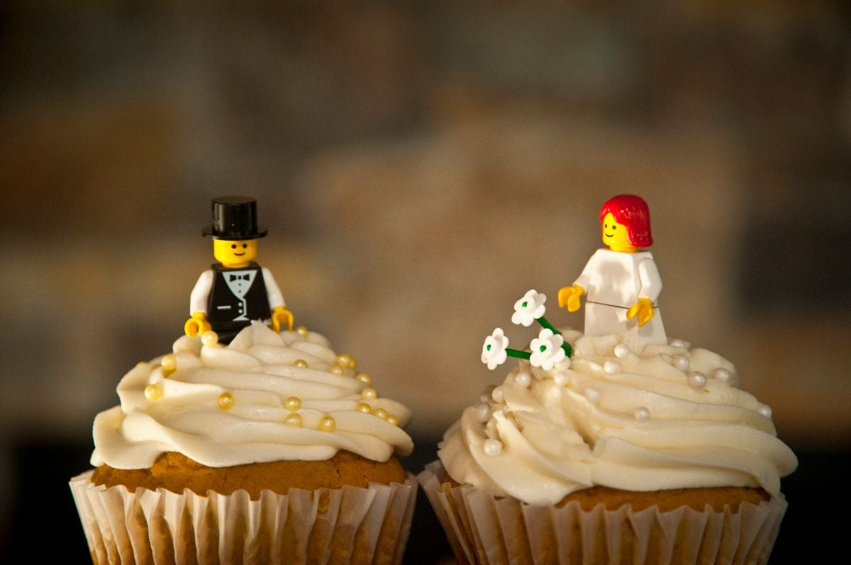 Lego bride and groom figurines on two vanilla cupcakes