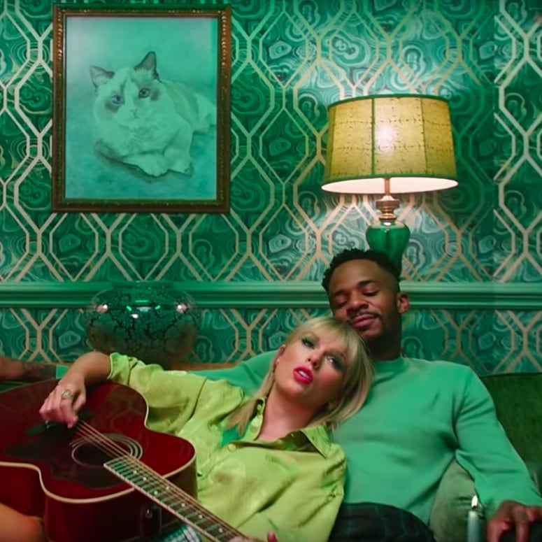Taylor Swift in the Lover music video laying on her lover, holding a guitar