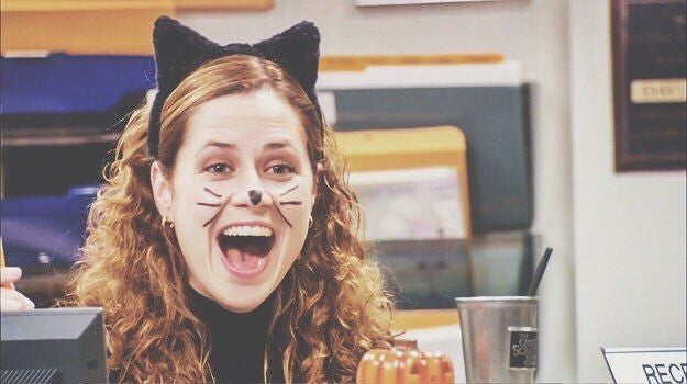 A woman with cat ears on has her eyes and mouth wide open