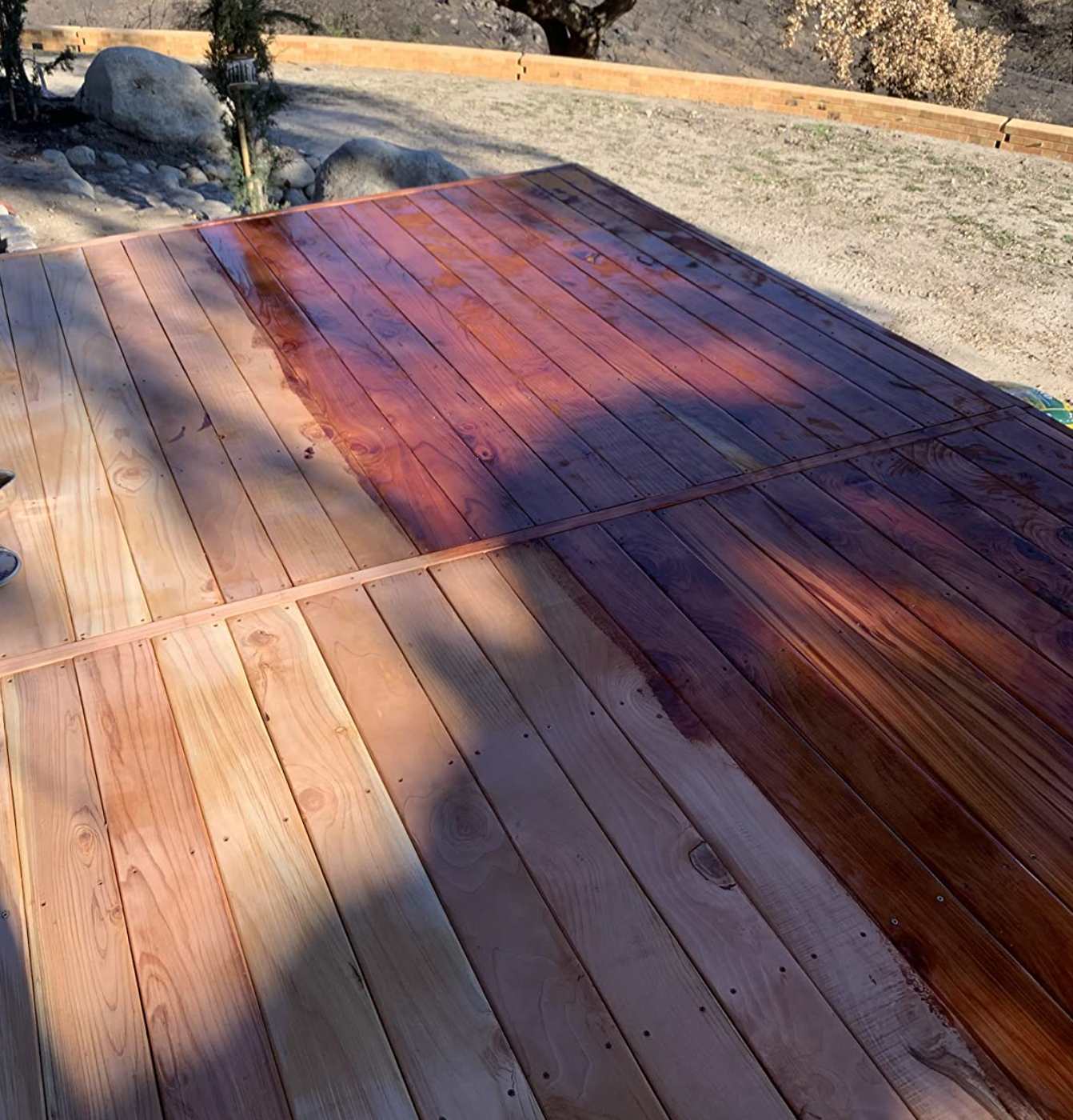 reviewer image of deck half stained, with the half-stained side vibrant and bright