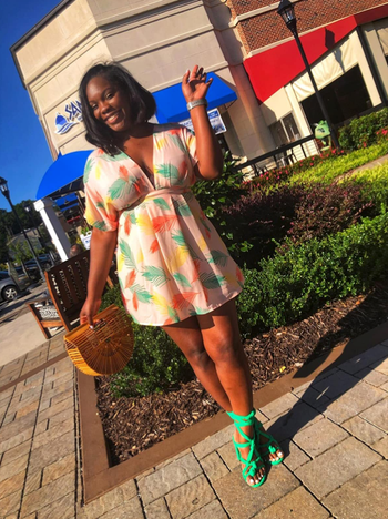 reviewer wearing the dress with bright green pumps