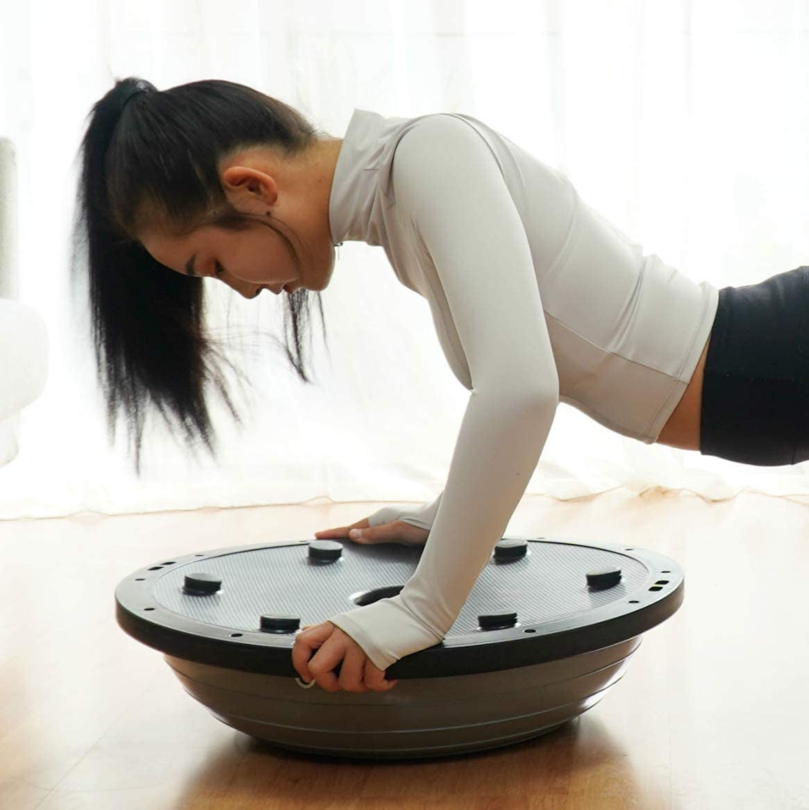 model in plank position on balance ball trainer