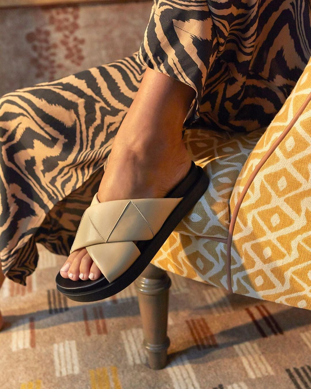 the slide with beige criss-cross thick straps and black footbed and sole