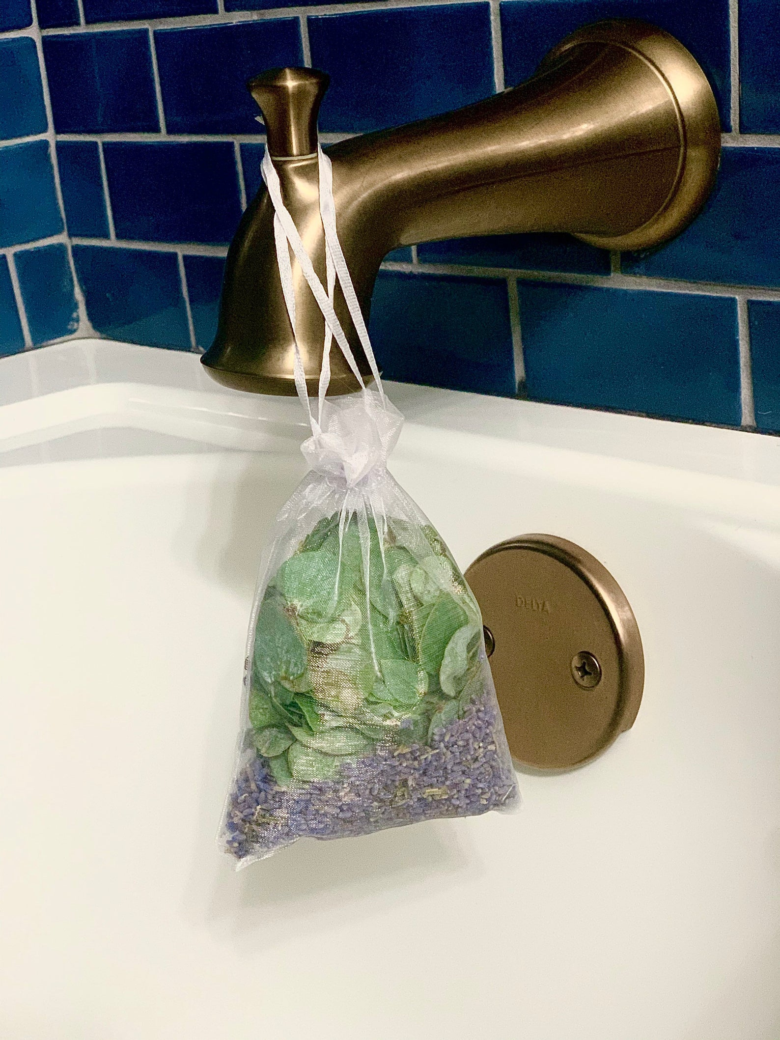 a pouch filled with eucalyptus and lavender hanging on a shower nozzle