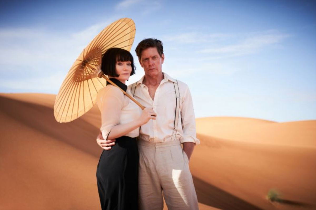 A woman and man stand in the desert
