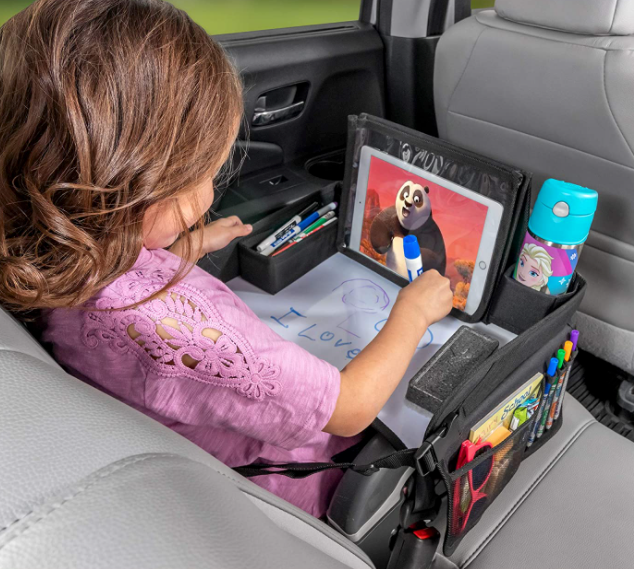 toddler in car seat with the tray placed over them while they draw and watch movie on tablet
