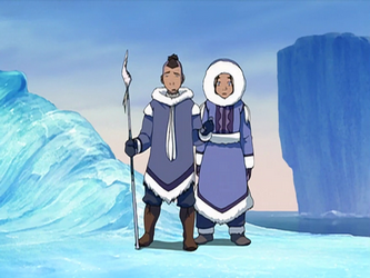 A man and woman stand in an icy landscape. They are both wearing thick, long coats with fur around the neck and sleeves