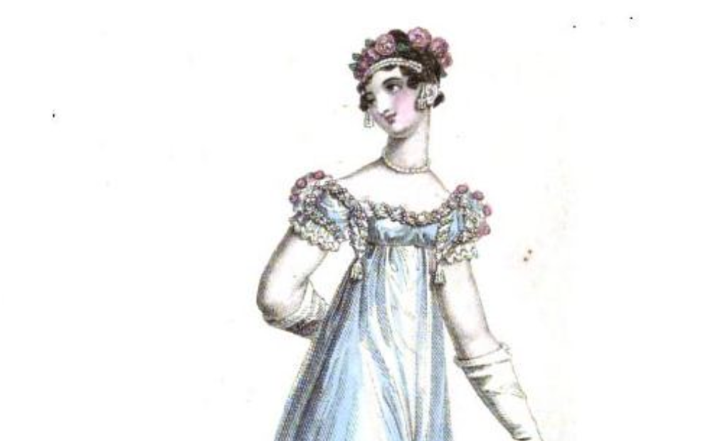 A woman with curly hair wears flowers atop her head. She also wears a dress with puffy sleeves and a collar lined with flowers. She also wears a pearl necklace
