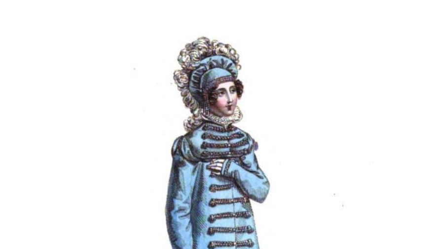 A woman wears feathers atop a hat on top of her curly hair. She also wears a long-sleeved dress with rope-looking string across her chest and stomach