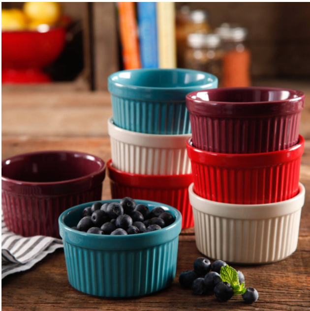 Multiple ramekins in red, maroon, cream, and turquoise. One of the turquoise ones is filled with blueberries