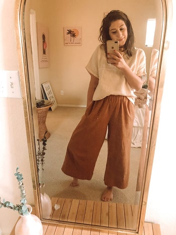 reviewer wearing the blouse with wide pants