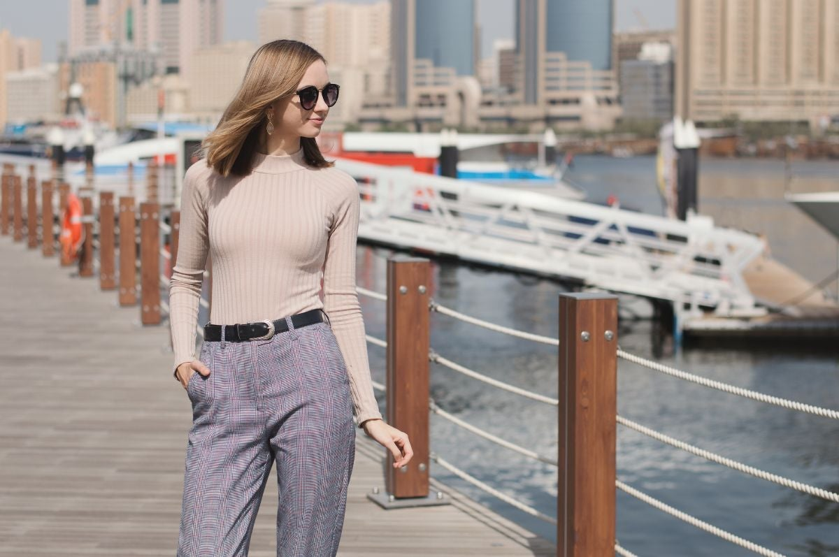 Someone wears a light colored turtleneck with belted high-waisted pants