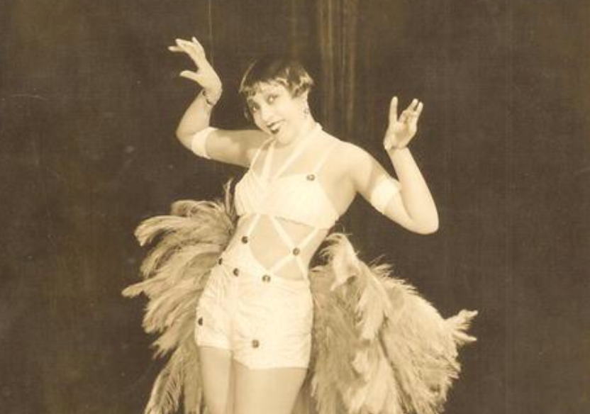 A woman with a haircut that stops above her ears holds her hands up at 90 degree angles. She is wearing a bra that is attached to a pair of shorts with strings and feathers coming out the back of the outfit
