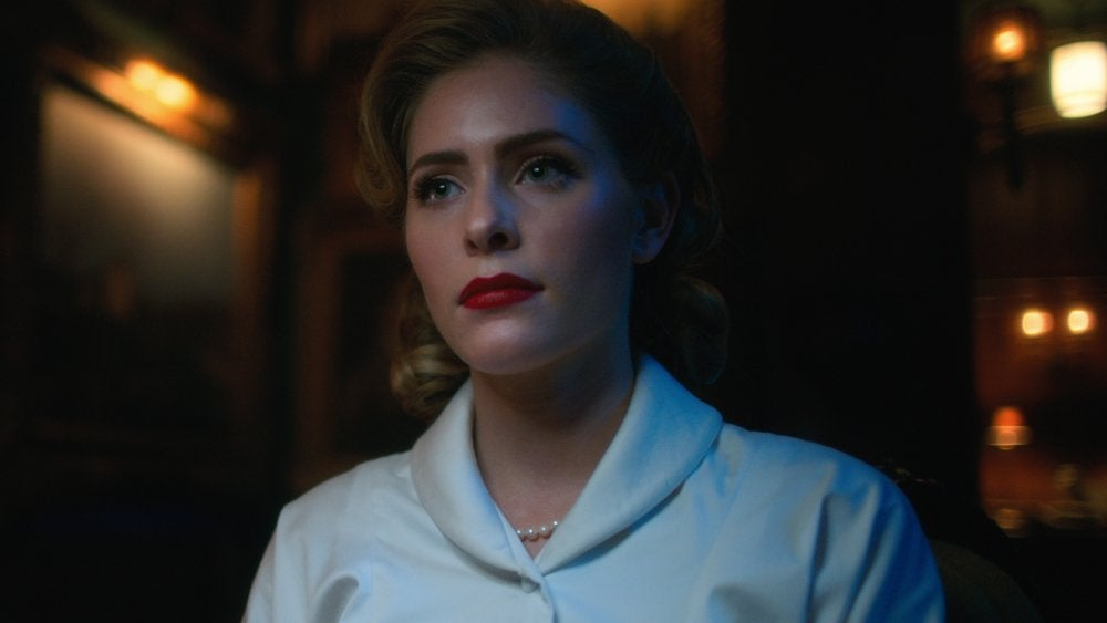 Grace is wearing bold lipstick and pearls, while standing in a dark room