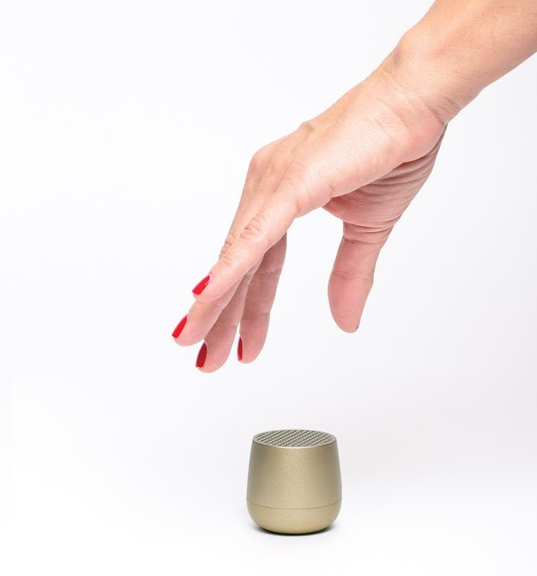 hand grabbing the small gold speaker