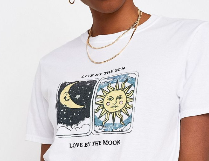 A close-up of a woman's neck wearing a thin gold chain and a t-shirt that has tarot cards on it