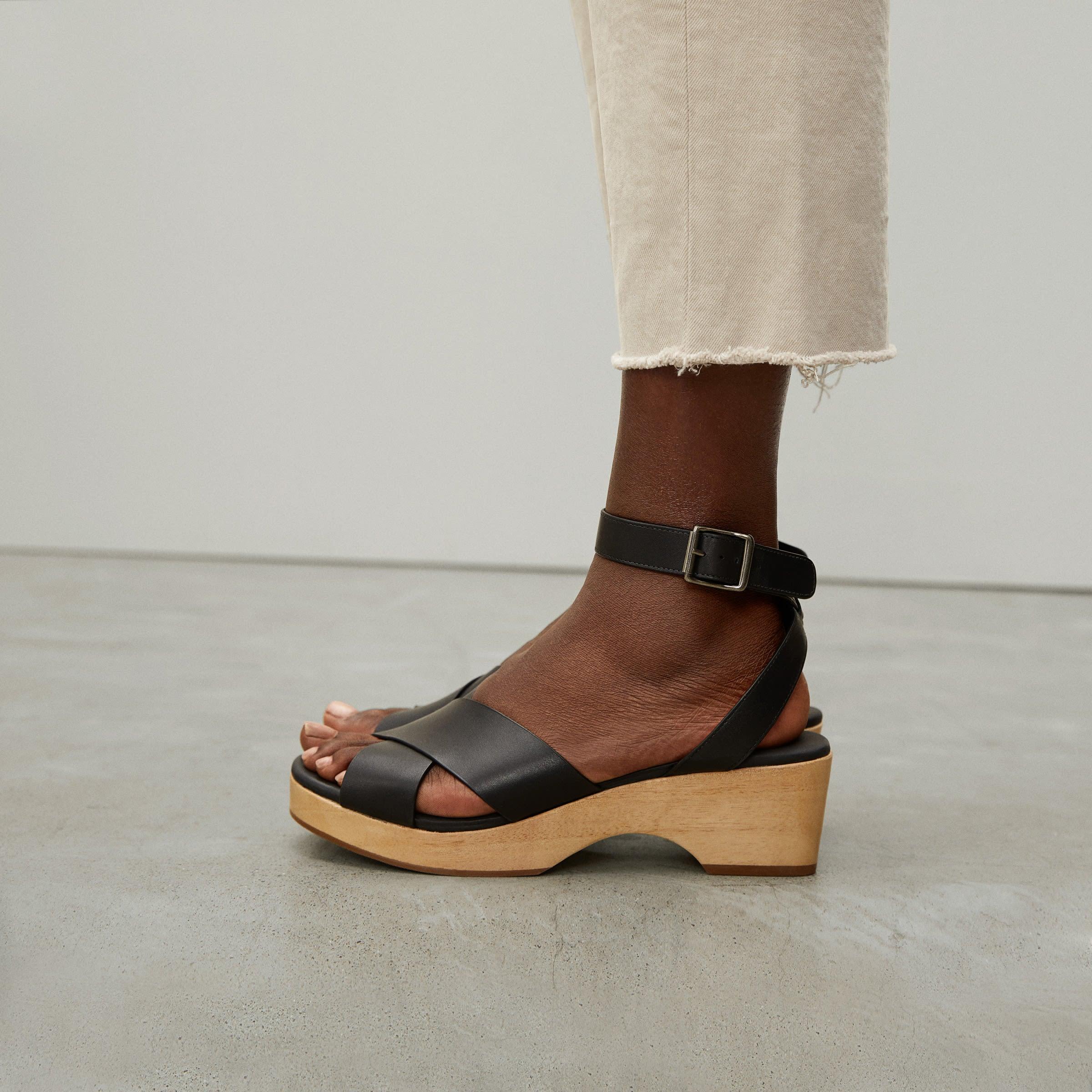 model wearing criss-cross strap in black with light wood sole