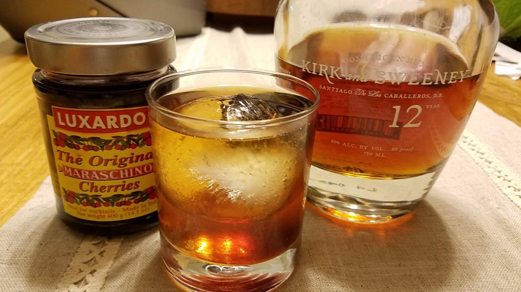 reviewer photo of the jar of cherries, a bottle of alcohol, and an old fashioned with a maraschino cherry in it