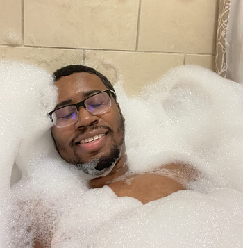 reviewer relaxing in a super bubbly bath