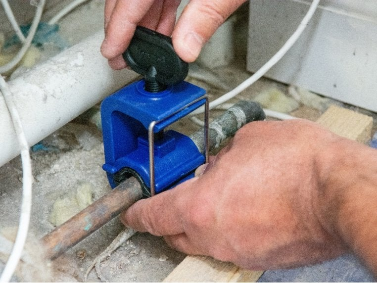 hands affixing clamp to a pipe