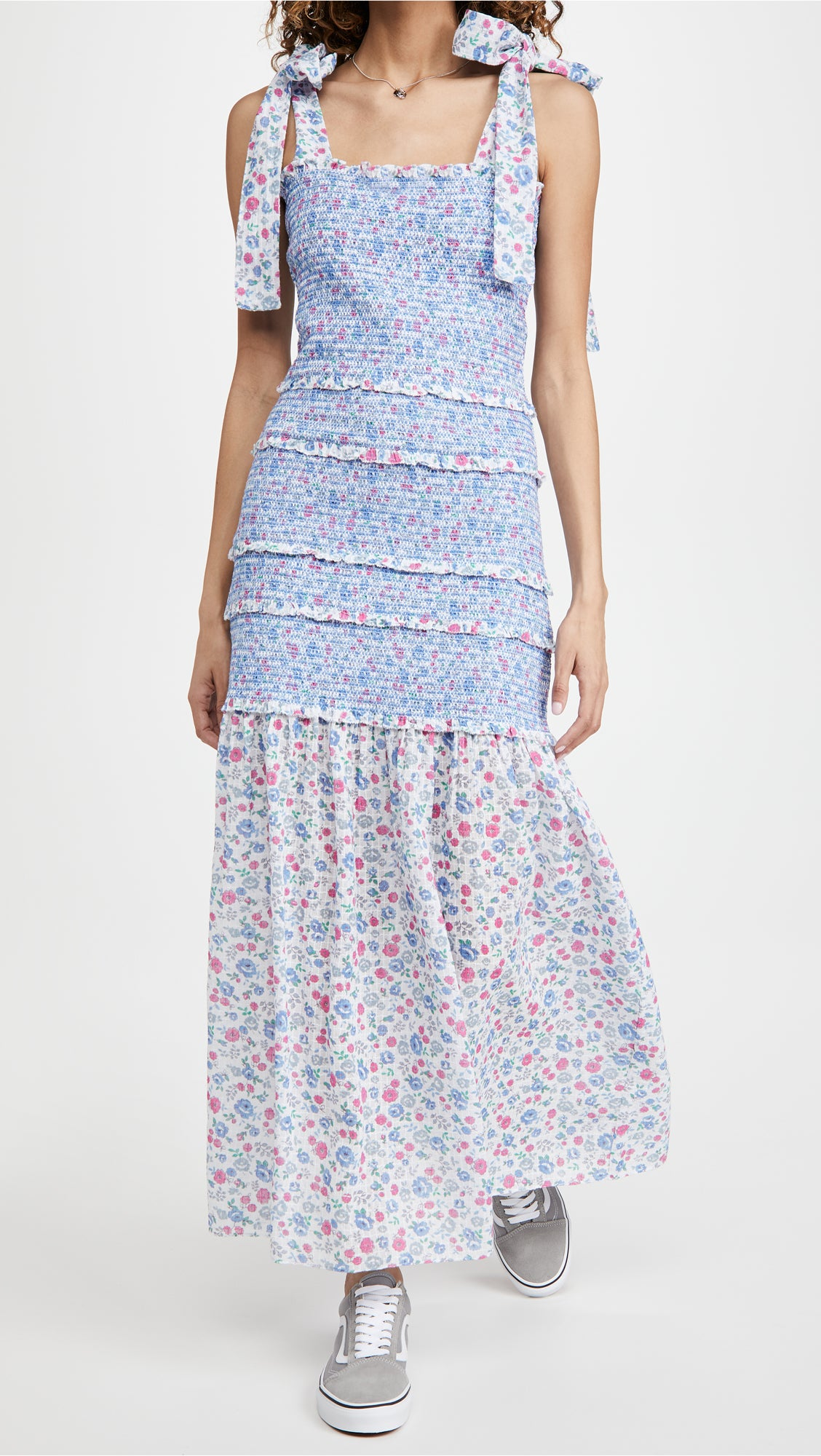 model in the blue, white, and pink floral dress with tie ribbon straps