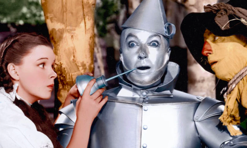 A girl with braids and a scarecrow look at a tin man