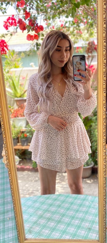 a reviewer wearing the romper in white and black polka dots
