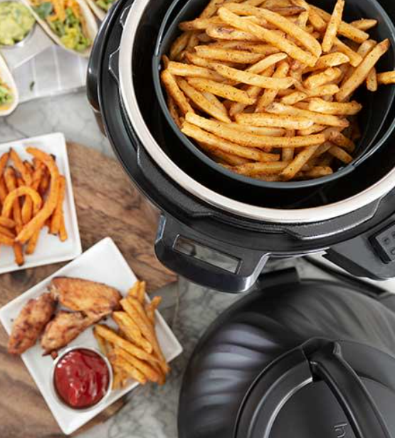 A Instant Pot with French fries in it and a plate of chicken and fries with ketchup
