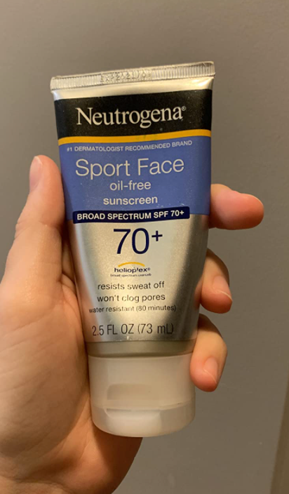 hand holding the tube of sunscreen