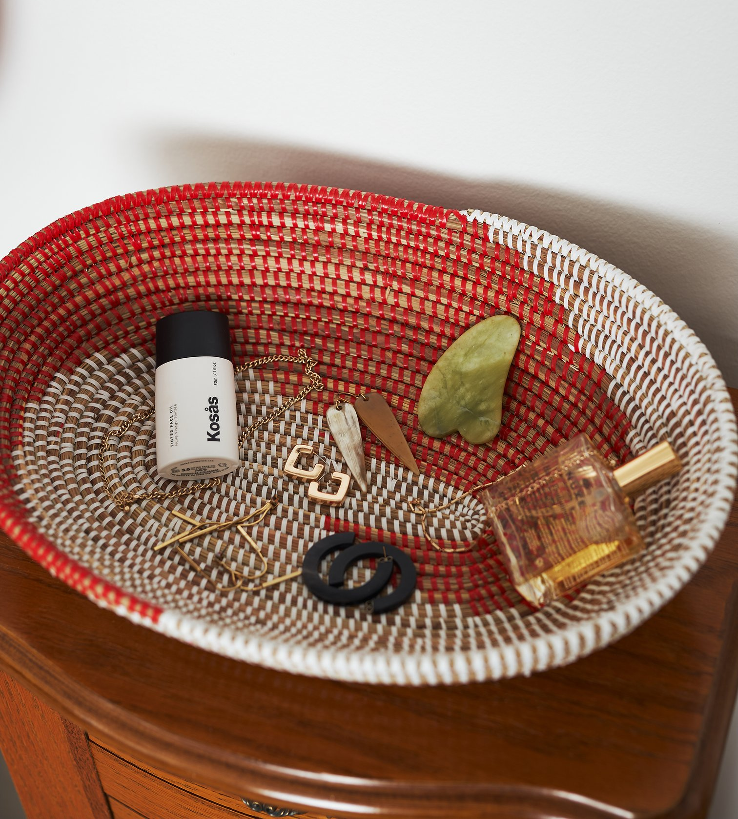 The oval red and white woven bowl with jewelry, a gua sha, perfume, and a cosmetics bottle in it
