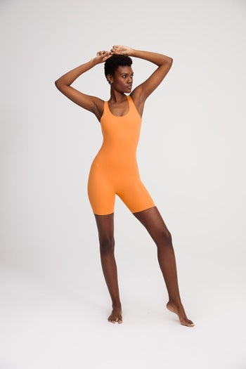 front view of a model wearing the unitard in orange